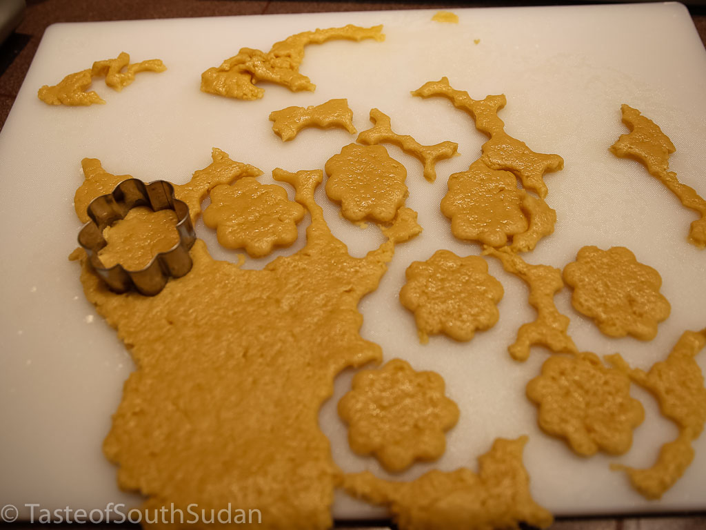 Making Christmas cookies, using cookie cutters.